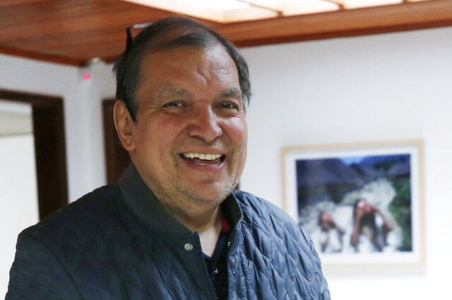 Associated Press reporter Cesar Garcia poses for a photo on his 20 year anniversary with the AP at his office in Bogota, Colombia, Friday, May 31, 2019. Garcia, a veteran reporter who ventured across Colombia to tell the story of the nation's armed conflict, has died at age 61. (AP Photo/Fernando Vergara)