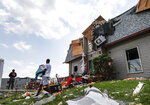 Residents remove belongings from their damaged homes at the River's Edge apartment complex, Tuesday, May 28, 2019, in Dayton, Ohio, the day after a tornado struck the city. (AP Photo/John Minchillo)