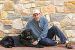 """Philip Tedeschi, director emeritus of the Institute for Human-Animal Connection at the University of Denver, poses with his dog, Samara, on  campus in Denver on July 25, 2018. In the eyes of the law, pets are property when it comes to divorce. But new ways of working out custody of the dog, cat or parrot have sprung up in recent years. There are special mediators and a push for """"petnups"""" to avoid courtroom disputes. (Jess Blackwell Photography/Rover.com via AP)."""