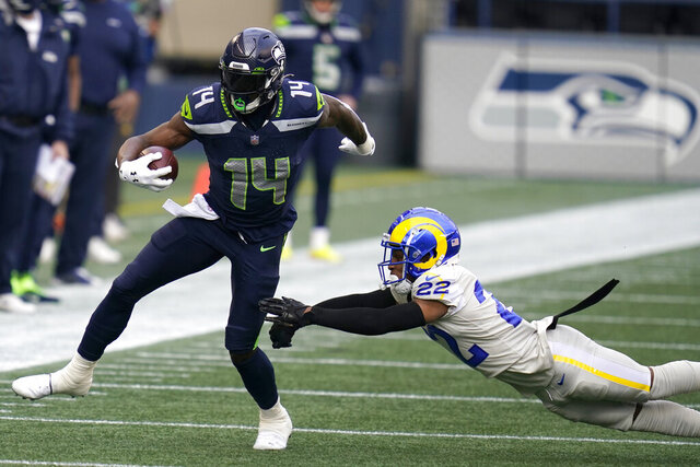 Seattle Seahawks wide receiver DK Metcalf (14) runs after a reception as Los Angeles Rams cornerback Troy Hill (22) attempts the tackle during the first half of an NFL football game, Sunday, Dec. 27, 2020, in Seattle. (AP Photo/Elaine Thompson)