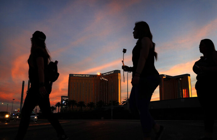 FILE - In this April 1, 2018 file photo, people carry flowers as they walk near the Mandalay Bay hotel and casino during a vigil for victims and survivors of a mass shooting in Las Vegas. MGM Resorts International has sued hundreds of victims of the deadliest mass shooting in modern U.S. history in a bid to avoid liability for the gunfire that rained down from its Mandalay Bay casino-resort in Las Vegas. The company argues in lawsuits filed Friday, July 13, 2018, in Nevada and California that it has
