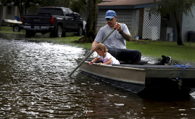 Lemay Acosta and his daughter Layla,2, take a boat ride in his flooded neighborhood in Plantation, Fla. a day after Tropical Storm Eta made landfall in the Florida Keys and flooded parts of South Florida, Monday, Nov. 9, 2020. South Florida will experience the high winds, rain and chance of tornadoes into Monday. (Carline Jean/South Florida Sun-Sentinel via AP)