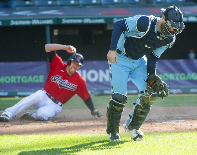 Toronto Blue Jays' Danny Jansen catches the throw but too far from home plate to tag Cleveland Indians' Bradley Zimmer as he scores the winning run on a sacrifice fly by Jose Ramirez during the seventh inning of the second baseball game of a doubleheader in Cleveland, Sunday, May 30, 2021. (AP Photo/Phil Long)