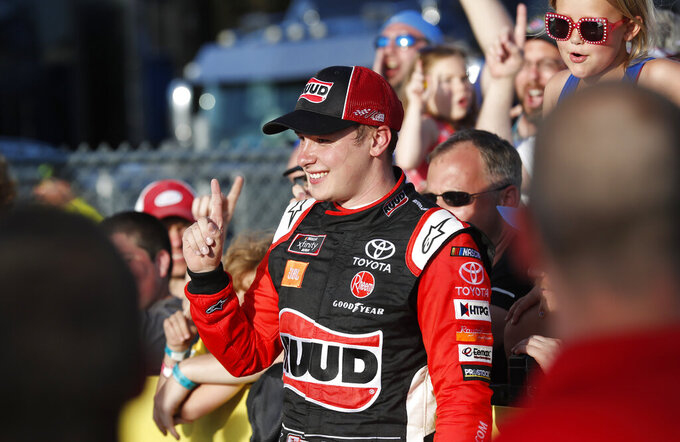 FILE - In this June 16, 2019, file photo, Christopher Bell celebrates with fans in Victory Lane after winning a NASCAR Xfinity Series auto race at Iowa Speedway in Newton, Iowa. Bell says he has re-signed with Joe Gibbs Racing for 2020, but he is not sure if he will be staying in the NASCAR Xfinity Series or moving up to the Cup Series. He won at Iowa Speedway on June 16 for his fourth Xfinity victory this season and second straight in Newton. (AP Photo/Charlie Neibergall, File)