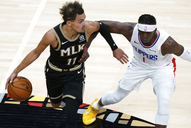Atlanta Hawks guard Trae Young (11) drives against Los Angeles Clippers guard Reggie Jackson (1) in the second half of an NBA basketball game Tuesday, Jan. 26, 2021, in Atlanta. (AP Photo/John Bazemore)