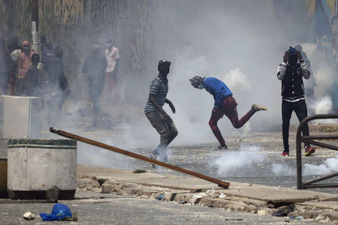 A demonstrators runs amid tear gas smoke during protests against the arrest of opposition leader and former presidential candidate Ousmane Sonko in Dakar, Senegal, Friday, March 5, 2021. Days of violent protests in Senegal have killed at least one person, local reports say, as young people take to the streets nationwide in support of the main opposition leader who was detained Wednesday. (AP Photo/Leo Correa)