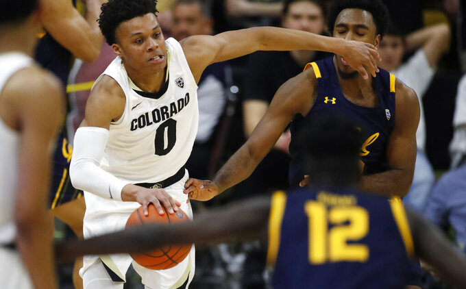 Colorado guard Shane Gatling, left, hits California guard Kareem South while picking up the ball in the second half of an NCAA college basketball game Thursday, Feb. 6, 2020, in Boulder, Colo. (AP Photo/David Zalubowski)