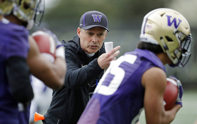 Washington head coach Chris Petersen talks to players as they run drill during the first day of spring NCAA college football practice, Wednesday, April 3, 2019, in Seattle. (AP Photo/Ted S. Warren)