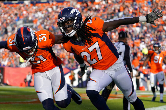 Denver Broncos cornerback Davontae Harris (27) celebrates with free safety Justin Simmons (31) after breaking up a pass in the end zone during the first half of NFL football game against the Cleveland Browns, Sunday, Nov. 3, 2019, in Denver. (AP Photo/Jack Dempsey)