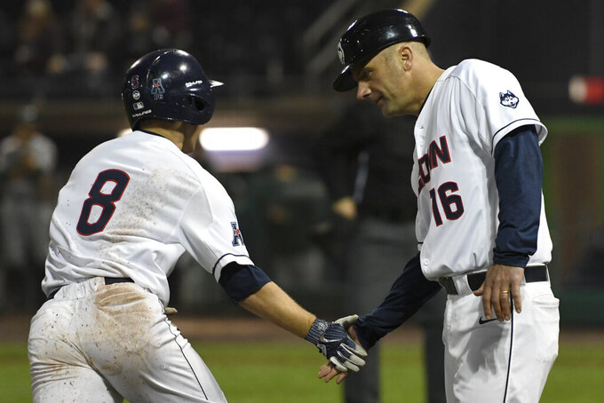 UConn head coach Jim Penders congratulates Michael Woodworth (8) as he rounds the bases in the eighth inning of an NCAA college baseball game against Tulane in Hartford, Conn., in this April 27, 2018, photo. Penders, the nephew of former college hoops coach Tom Penders, credits Connecticut's basketball programs and their combined 15 national titles, with creating an athletics culture that has helped him recruit top players to Storrs and convince officials to build his team's just opened state-of-the art Elliot Ballpark, which comes complete with an artificial turf field and heated benches. (John Woike/Hartford Courant via AP)