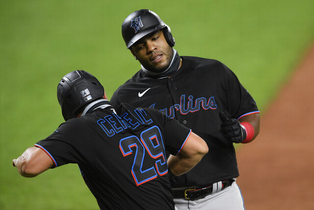 Miami Marlins' Francisco Cervelli (29) greets Jesus Aguilar, back, after they both scored on a Brian Anderson single during the third inning of a baseball game against the Baltimore Orioles, Thursday, Aug. 6, 2020, in Baltimore. (AP Photo/Nick Wass)