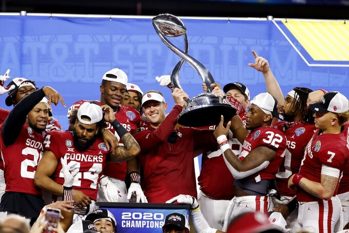 Oklahoma coach Lincoln Riley stands surrounded by the team as he holds up the trophy following Oklahoma's 55-20 win over Florida in the Cotton Bowl NCAA college football game in Arlington, Texas, Wednesday, Dec. 30, 2020. (AP Photo/Michael Ainsworth)