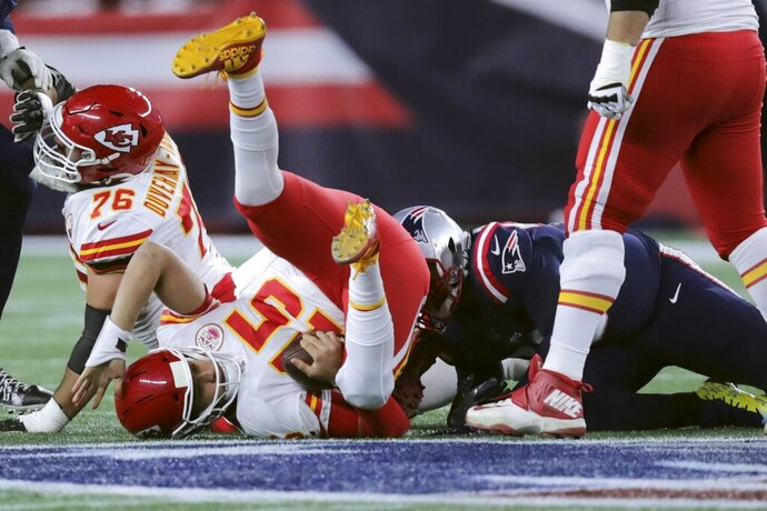 FILE - In this Sunday, Dec. 8, 2019, file photo, Kansas City Chiefs quarterback Patrick Mahomes lands on the turf after he was sacked by New England Patriots defensive tackle Adam Butler, right rear, in the first half of an NFL football game in Foxborough, Mass. In three previous meetings with Kansas City's Patrick Mahomes, the Patriots defense has had its most success when it's been able to force turnovers and get pressure on him. But that's easier said than done against a quarterback who has yet commit a turnover this season and is completing a career-high 68% of his passes.(AP Photo/Charles Krupa, File)