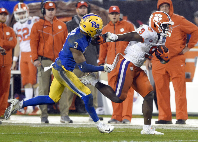 Clemson's Travis Etienne (9) runs past Pittsburgh's Damar Hamlin (3) in the first half of the Atlantic Coast Conference championship NCAA college football game in Charlotte, N.C., Saturday, Dec. 1, 2018. (AP Photo/Mike McCarn)