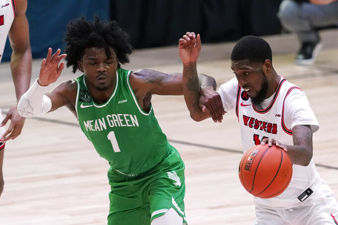 Western Kentucky guard Taveion Hollingsworth drives past North Texas guard Mardrez McBride (1) during the second half of the championship game in the NCAA Conference USA men's basketball tournament Saturday, March 13, 2021, in Frisco, Texas. (AP Photo/Tony Gutierrez)