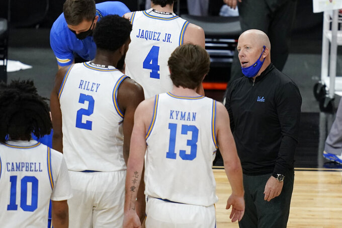 UCLA head coach Mick Cronin, right, speaks with players during the first half of an NCAA college basketball game against Oregon State in the quarterfinal round of the Pac-12 men's tournament Thursday, March 11, 2021, in Las Vegas. (AP Photo/John Locher)