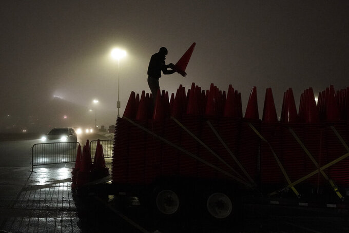 Zach Wade stacks traffic cones onto a trailer as fog envelopes a parking lot at Arrowhead Stadium after an NFL football game between the Los Angeles Chargers and the Kansas City Chiefs, Sunday, Jan. 3, 2021, in Kansas City, Mo. The cones were among 7,000 placed to block off every other parking space at the stadium in order to maintain social distancing in an attempt to stop the spread of the new coronavirus. (AP Photo/Charlie Riedel)