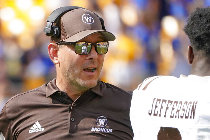 Western Michigan head coach Tim Lester talks to running back La'Darius Jefferson (3) as his team plays against Pittsburgh during the second half of an NCAA college football game, Saturday, Sept. 18, 2021, in Pittsburgh. Western Michigan won 44-41.(AP Photo/Keith Srakocic)