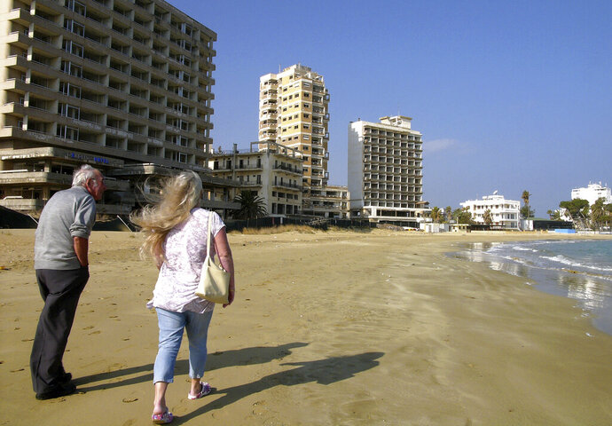 FILE - Friday, Jan.17, 2014 file photo, a couple walk on the beach by the deserted hotels in an area used by the Turkish military in the Turkish occupied area in abandoned coastal city of Varosha, in Famagusta, in southeast of island of Cyprus. Cyprus government spokesman Kyriakos Koushos says on Tuesday, Oct. 6, 2020, formal protests will be lodged at the United Nations, the European Union and other international organizations over Turkey's decision to open up to the public a stretch of beach in fenced-off Varosha. Koushos said the move contravenes international law and U.N. Security Council resolutions on Varosha that has remained uninhabited for 46 years. (AP Photo/Petros Karadjias, File)