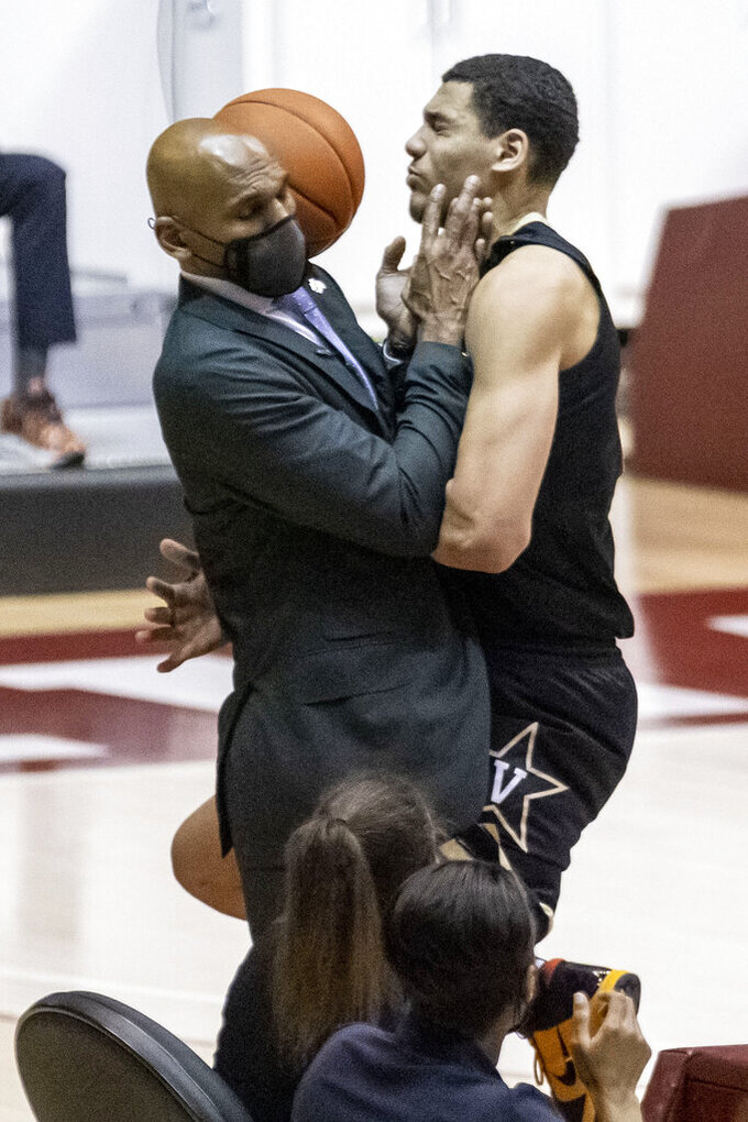 Vanderbilt forward Dylan Disu (1) collides with Vanderbilt head coach Stackhouse while chasing a long inbounds pass during the second half of an NCAA basketball game against Alabama on Saturday, Feb. 20, 2021, in Tuscaloosa, Ala. (AP Photo/Vasha Hunt)