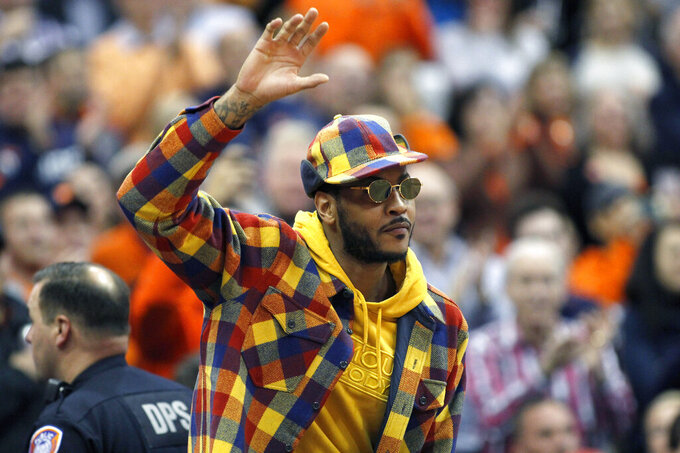 Former Syracuse basketball great Carmelo Anthony waves to the crowd during the first half of an NCAA college basketball game against Virginia in Syracuse, N.Y., Wednesday, Nov. 6, 2019. (AP Photo/Nick Lisi)