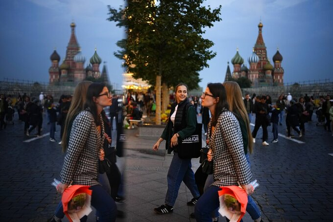People walk reflecting in a mirror installation after sunset in Red Square in Moscow, Russia, Sunday, Sept. 12, 2021. (AP Photo/Alexander Zemlianichenko)