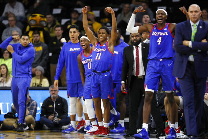FILE - In this Nov. 11, 2019, file photo, DePaul guard Charlie Moore (11) and teammates celebrate on the bench during the first half of the team's NCAA college basketball game against Iowa in Iowa City, Iowa. The Blue Demons are 8-0 for the first time since the 1986-87 team won its first 16 games and turning heads in a way the once-proud program hasn't in years. With NCAA runner-up Texas Tech visiting on Wednesday, they could really open some eyes. DePaul already has road wins over Iowa, Boston College and Minnesota. (AP Photo/Charlie Neibergall, File)