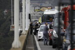 Police stand at the site where an armed man who took dozens of hostages on a bus was shot dead, on the bridge connecting the city of Niteroi to Rio de Janeiro , Brazil, Tuesday, Aug. 20, 2019. An armed man holding dozens of people hostage on a public bus and threatening to set the vehicle on fire was seized by police after a four-hour long standoff, Brazilian police said.  (AP Photo/Leo Correa)