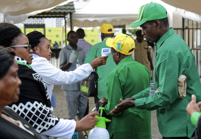 FILE - In this July 11, 2020, file photo, party members have their temperature checked and sanitize their hands as a precaution against the coronavirus at the national congress of the ruling Chama cha Mapinduzi (CCM) party in Dodoma, Tanzania. Opposition politicians on Wednesday March 10 2021, are raising questions about the health of Tanzania's COVID-19-denying president John Magufuli, as he has not been seen in public for more than a week and there has been no responce to questions from The Associated Press about Magufuli's health and whereabouts. (AP Photo, File)
