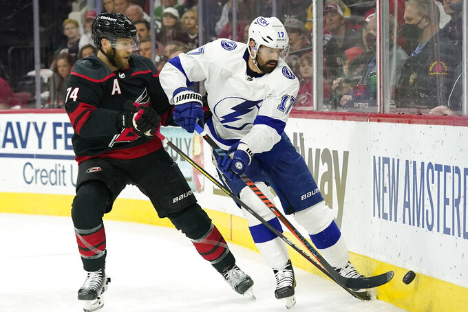 Carolina Hurricanes defenseman Jaccob Slavin (74) and Tampa Bay Lightning left wing Alex Killorn (17) chase the puck during the first period in Game 5 of an NHL hockey Stanley Cup second-round playoff series in Raleigh, N.C., Tuesday, June 8, 2021. (AP Photo/Gerry Broome)