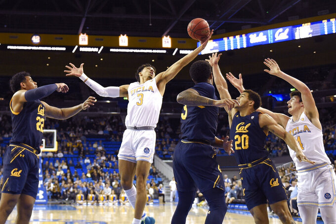 UCLA guard Jules Bernard, second from left, grab a rebound away from California forward Andre Kelly, left, guard Paris Austin, center, and guard Matt Bradley, second from right, as guard Jaime Jaquez Jr. reaches in during the first half of an NCAA college basketball game Sunday, Jan. 19, 2020, in Los Angeles. (AP Photo/Mark J. Terrill)