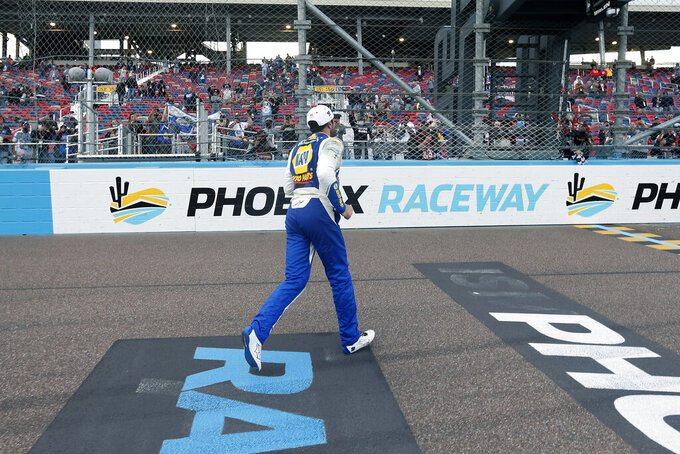 Chase Elliott runs to the starters stand to get the checkered flag after his season championship victory in the NASCAR Cup Series auto race at Phoenix Raceway, Sunday, Nov. 8, 2020, in Avondale, Ariz. (AP Photo/Ralph Freso)