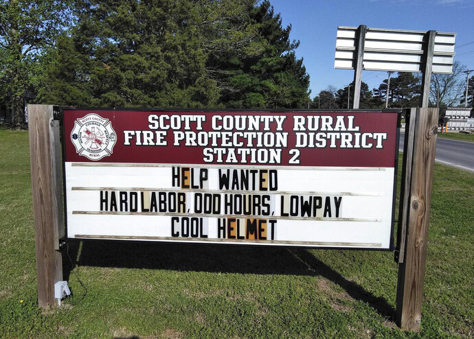 This April 20, 2019 photo provided by the Scott County, Mo., Rural Fire Protection District shows a novel approach the district is using to recruit new firefighters. The county is trying to recruit new firefighters with its sales pitch, saying in signs posted outside one of its stations that the job offers