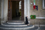 A friar leaves after voting at a polling station, in Rome, Sunday, Sept. 20, 2020. On Sunday and Monday Italians are called to vote nationwide in a referendum to confirm a historical change to the country's constitution to drastically reduce the number of Members of Parliament from 945 to 600. Eighteen million of Italian citizens will  also vote on Sunday and Monday to renew local governors in seven regions, along with mayors in approximately 1,000 cities.(AP Photo/Andrew Medichini)