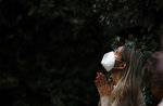 A woman attends Mass outside the Schoenstatt shrine during Easter in Buenos Aires, Argentina, Thursday, April 1, 2021. The Mass was held outside to avoid the spreading of COVID-19. (AP Photo/Natacha Pisarenko)