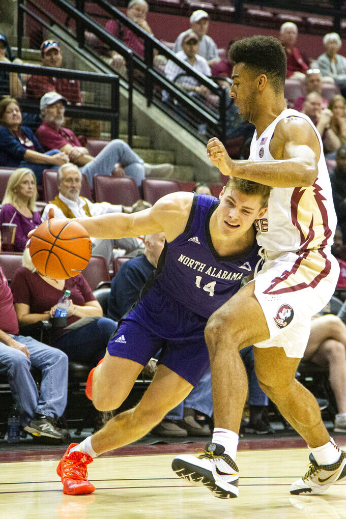 North Alabama forward Payton Youngblood, left, tries to get past Florida State guard Anthony Polite, right, in the first half of an NCAA college basketball game in Tallahassee, Fla., Saturday, Dec. 28, 2019. (AP Photo/Mark Wallheiser)
