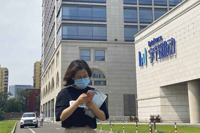 FILE - A woman uses her phone as she passes by the ByteDance headquarters in Beijing, China, on Friday, Aug. 7, 2020. The Chinese government is complicating the U.S.-government-ordered sale of U.S. TikTok assets.  China on Friday, Aug. 28, 2020 introduced export restrictions on artificial intelligence technology, seemingly including the type that TikTok uses to choose which videos to spool up to its users. That means TikTok's Chinese owner, ByteDance, would have to obtain a license to export any restricted technologies to a foreign company. (AP Photo/Ng Han Guan)