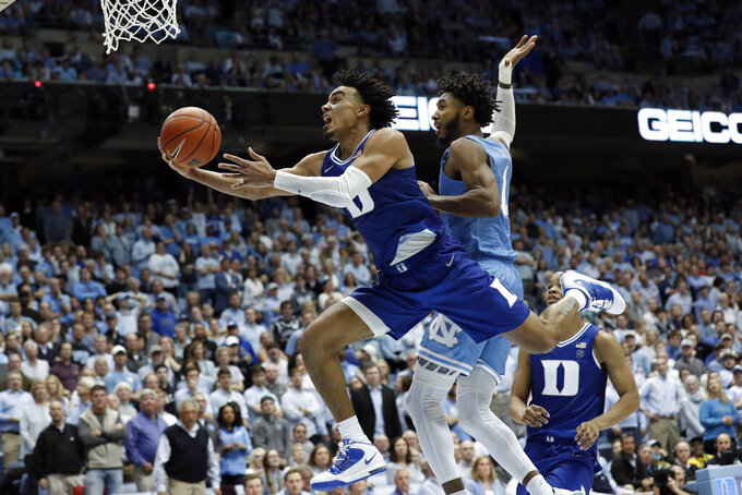 FILE - In this Feb. 8, 2020, file photo, Duke guard Tre Jones drives to the basket against North Carolina guard Leaky Black (1) during the second half of an NCAA college basketball game in Chapel Hill, N.C. Tre Jones was selected to the Associated Press All-ACC team selected Tuesday, March 10, 2020.  (AP Photo/Gerry Broome, File)