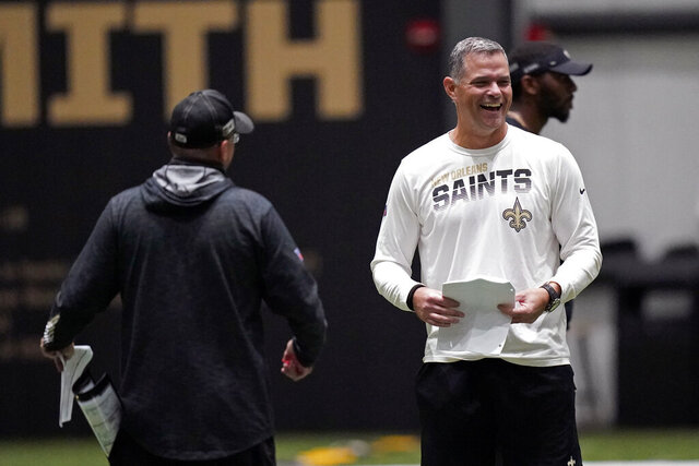 FILE - In this Sept. 2, 2020, file photo, New Orleans Saints quarterbacks coach Joe Lombardi, right, laughs with offensive coordinator Pete Carmichael during practice at their NFL football training facility in Metairie, La. The Los Angeles Chargers announced on Monday, Jan. 25, 2021, they have agreed to terms with Lombardi as offensive coordinator, Renaldo Hill as defensive coordinator and Derius Swinton II as special teams coordinator. (AP Photo/Gerald Herbert, Pool, File)