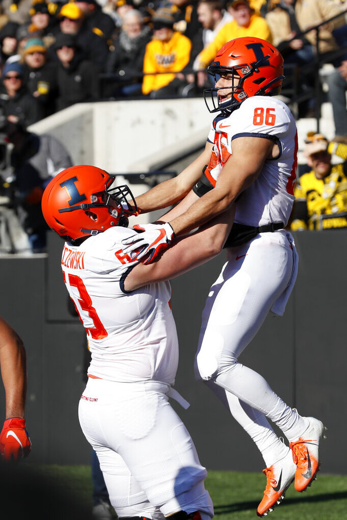 Illinois wide receiver Donny Navarro celebrates with teammate Alex Palczewski, left, after catching a 31-yard touchdown pass during the first half of an NCAA college football game against Iowa, Saturday, Nov. 23, 2019, in Iowa City, Iowa. (AP Photo/Charlie Neibergall)