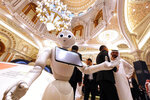 A robot welcomes participants to the Future Investment Initiative forum,