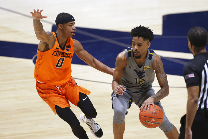 West Virginia guard Taz Sherman (12) is defended by Oklahoma State guard Avery Anderson III (0) during the second half of an NCAA college basketball game Saturday, March 6, 2021, in Morgantown, W.Va. (AP Photo/Kathleen Batten)