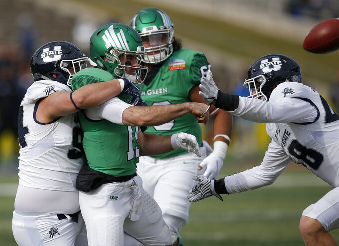 North Texas quarterback Quinn Shanbour (19) throws as he is sacked by Utah State nose guard Caden Andersen, left, during the first half of the New Mexico Bowl NCAA college football game in Albuquerque, N.M., Saturday, Dec. 15, 2018. (AP Photo/Andres Leighton)
