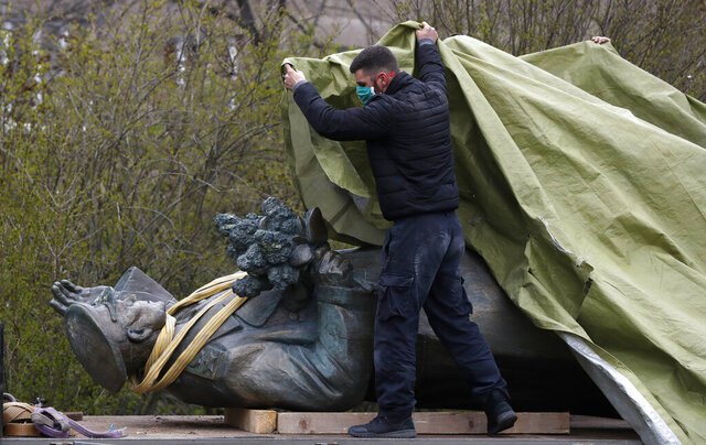 FILE - In this file photo taken on Friday, April 3, 2020, a worker covers the statue of a Soviet World War II commander Marshall Ivan Stepanovic Konev for removal from its site in Prague, Czech Republic. Relations between the Czech Republic and Russia have taken a turn for the worse in a series of disputes over the interpretation of historical events. Three Prague politicians whose recent actions upset Russia have been placed under police protection amid a media report that Russian intelligence services have been plotting to poison them with the deadly toxin ricin. Russia has opened a criminal investigation into Prague's removal of a war memorial to a World War II hero, among other actions that have tested diplomatic ties.  (AP Photo/Petr David Josek/File)