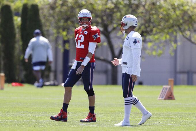 New England Patriots quarterback Tom Brady (12) speaks with kicker Stephen Gostkowski while warming up during an NFL football practice, Monday, Aug. 26, 2019, in Foxborough, Mass. (AP Photo/Steven Senne)