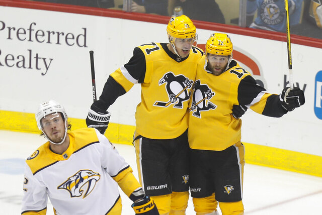 Pittsburgh Penguins' Bryan Rust (17) celebrates with Evgeni Malkin (71) after scoring against the Nashville Predators during the first period of an NHL hockey game Saturday, Dec. 28, 2019, in Pittsburgh. Nashville Predators' Ryan Johansen skates by at left.(AP Photo/Keith Srakocic)