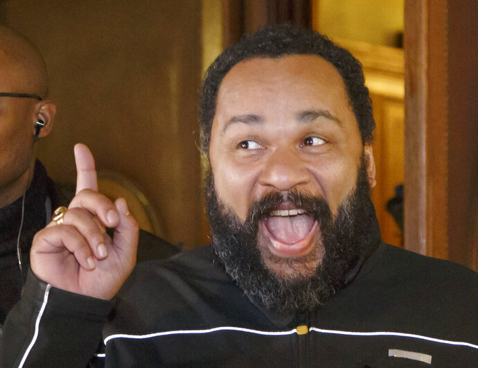 FILE - In this Feb.4, 2015 file photo, French comedian Dieudonne M'Bala M'Bala gestures to the media as he leaves a Paris court house. A French court has convicted Friday July 5, 2019 controversial comedian Dieudonne M'Bala M'Bala, found guilty in the past of anti-Semitism, on fraud and money laundering charges, and sentenced him to two years in prison. (AP Photo/Michel Euler, File)