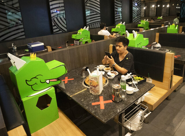 A customer uses a mobile phone while sitting with a cartoon dragon dolls the restaurant uses as space keepers for social distancing to help curb the spread of the coronavirus at shopping mall in Bangkok, Thailand, Monday, May 18, 2020. Thai authorities allowed department stores, shopping malls and other businesses to reopen from May 17, selectively easing restrictions meant to combat the coronavirus. (AP Photo/Sakchai Lalit)