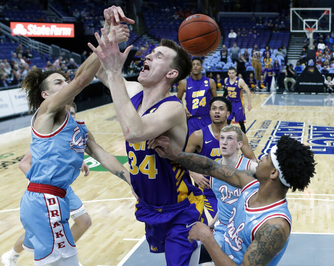 Northern Iowa's Luke McDonnell (34) loses control of the ball between Drake's Noah Thomas, left, and Anthony Murphy, right, during the first half of an NCAA college basketball game in the semifinal round of the Missouri Valley Conference tournament, Saturday, March 9, 2019, in St. Louis. (AP Photo/Jeff Roberson)