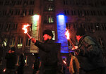 European Union and Bulgarian flags are projected on a building as people holding torches take part in the
